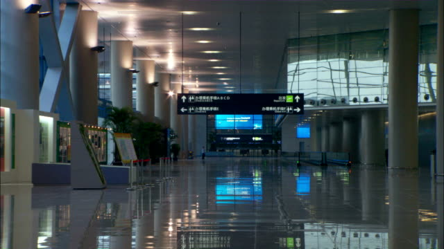 Wide Shot zoom-out - Signs point to airport terminals./Shanghai, China