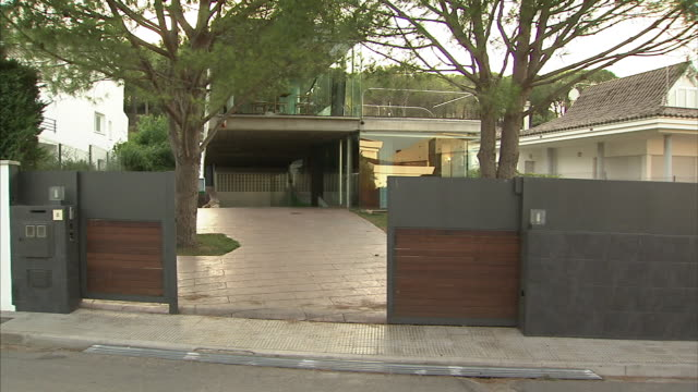 wide shot_static - a security gate closes in front of a modern home.   - cancello video stock e b–roll