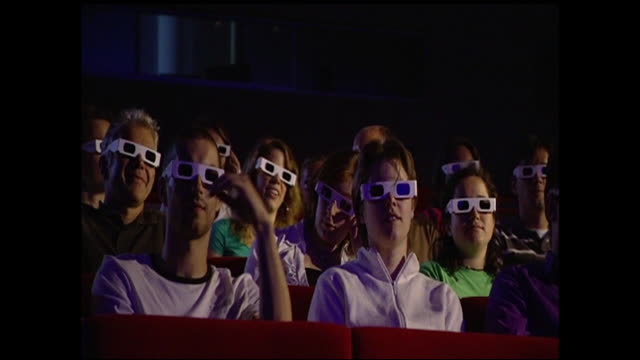 vídeos de stock, filmes e b-roll de wide shot_static - audience members wear 3-d glasses to have a realistic visual experience.   - óculos de terceira dimensão