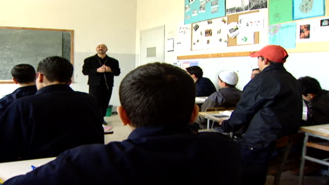 wide shotfrom the back of the classroom, of a druze sheikh teacher lecturing schoolboys. irfan is a druze religious school with five branches across... - シャイフ点の映像素材/bロール