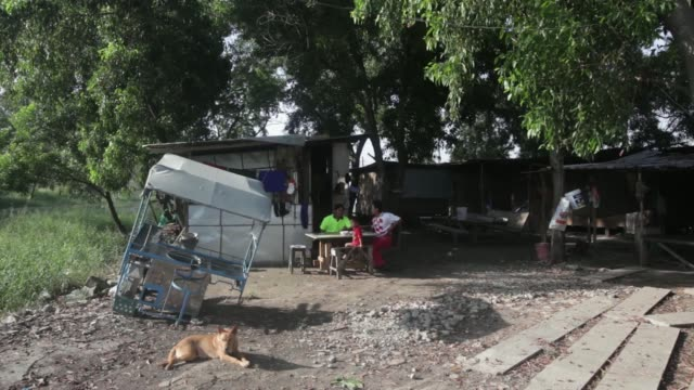 wide shots a family sits around a table for a meal outside their home in banwah ayutthaya province thailand on wednesday nov 27 a man sleeps by an... - makeshift stock videos and b-roll footage