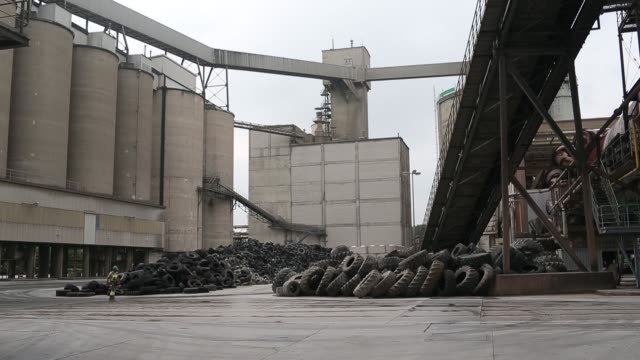 wide shots mounds of truck tires used to fuel the cement factory stand at heidelbergcement ags plant in ennigerloh, germany, on friday, aug 15 pan l... - beton stock-videos und b-roll-filmmaterial