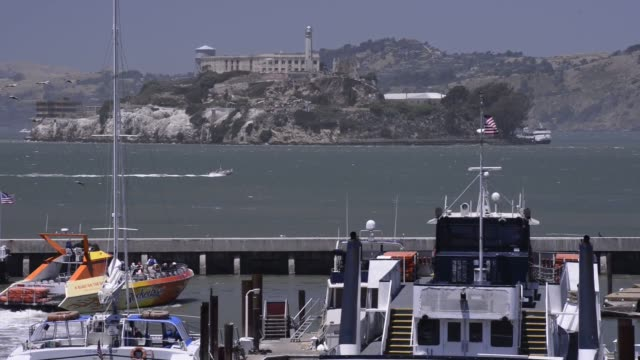 stockvideo's en b-roll-footage met wide shots of alcatraz island from fishermans wharf in san francisco california wide shot of tourists walking into pier 39 on fishermans wharf in san... - pier 39