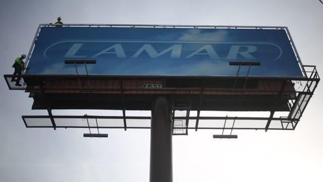 Wide shots of an employee of Lamar Advertising Co working to change an outdoor advertising billboard in Cincinnati Ohio US on Monday Feb 20 2017...