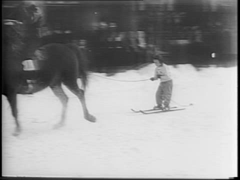 Wide shots of Army men skiing behind a trotting horse while a crowd looks on / Wide shot of skiers trying to catch a pig while on skis and attempting...
