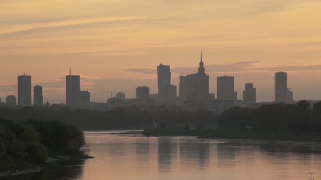 Wide shots of central Warsaw skyline viewed from Swietokrzyski Bridge over the Vistula river at dusk in Warsaw Poland on Monday June 16 Pan river and...