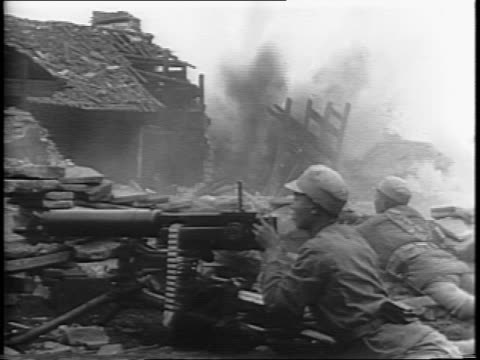 Wide shots of Chinese troops crouching and moving forward slowly amongst bombed out buildings and attempting to capture the city of Chong Te from the...
