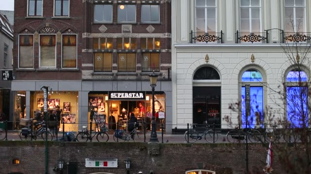 wide shots of fashion retailers and a cafe sitting along a canal in utrecht netherlands dutch retail utrecht netherlands on november 28 2013 in... - utrecht stock videos & royalty-free footage