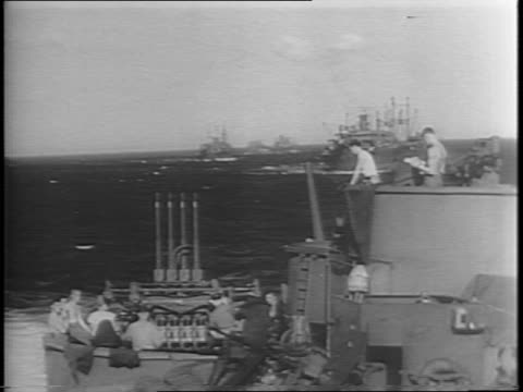 wide shots of row of battleships on the water / wide shot of deck of ship with gun turrets and anti aircraft weapons and soldiers manning positions /... - 船の一部点の映像素材/bロール