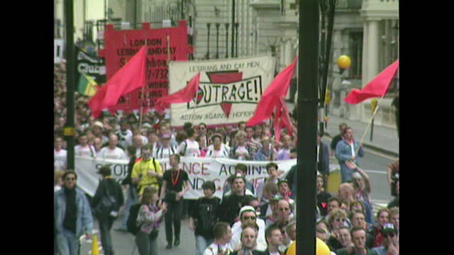 wide shots of the pride march in london in 1993, showing flags and prominent banners reading 'outrage' and 'stop violence against lesbians and gay... - local politics stock videos & royalty-free footage