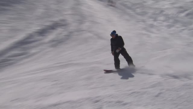 vídeos y material grabado en eventos de stock de wide shots skiers on mountainside children families walking through snow / skiers and snowboarder towards down slope / long shot man skiing down... - sochi