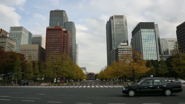 Wide shots traffic passes along road as commercial buildings stand on the skyline in the Marunouchi area of Tokyo Japan on Thursday Nov 14 Long shot...