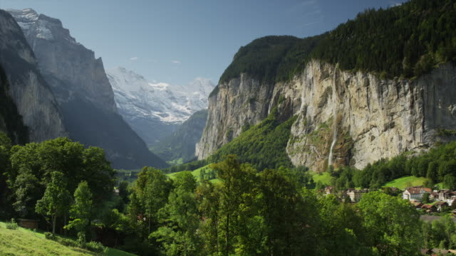 Wide shot/time lapse of remote village in mountain valley / Lauterbrunnan, Switzerland