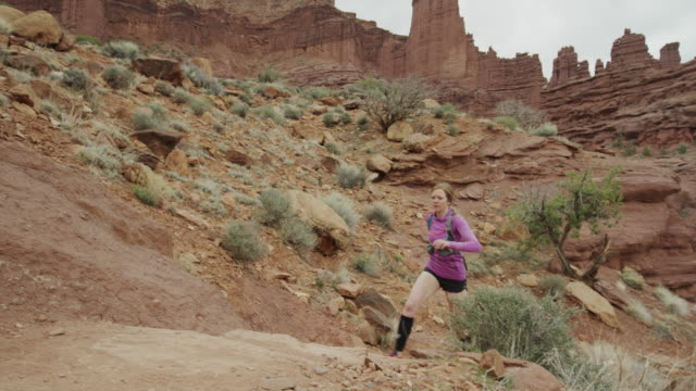 vidéos et rushes de wide slow motion high angle tracking shot of woman trail running in desert / fisher towers, utah, united states - dry clothes