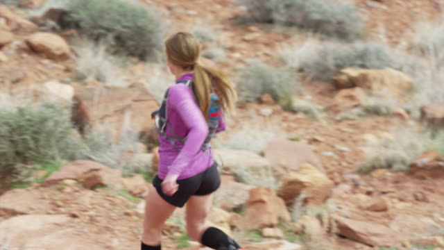 vídeos de stock, filmes e b-roll de wide slow motion high angle tracking shot of woman trail running in desert / fisher towers, utah, united states - calções de corrida
