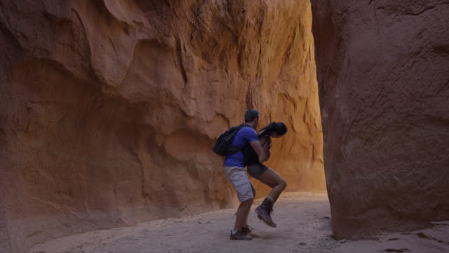 wide slow motion panning shot of affectionate couple hiking in narrow canyon / escalante, utah, united states - zungenkuss stock-videos und b-roll-filmmaterial