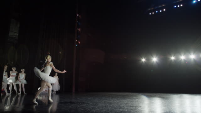 wide slow motion panning shot of ballerina leaping on stage / salt lake city, utah, united states - balletttänzer stock-videos und b-roll-filmmaterial