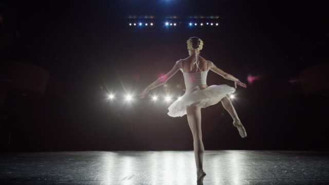 wide slow motion panning shot of ballerina spinning on stage / salt lake city, utah, united states - ballerina stock-videos und b-roll-filmmaterial