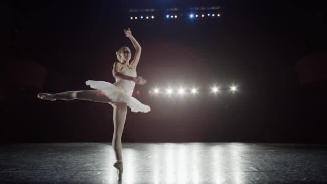 wide slow motion panning shot of ballerina spinning on stage / salt lake city, utah, united states - moderner tanz stock-videos und b-roll-filmmaterial