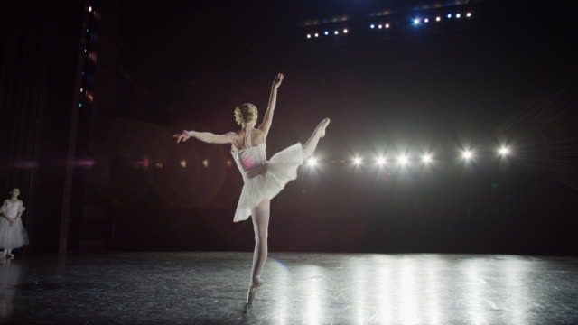 wide slow motion panning shot of ballerina spinning on stage / salt lake city, utah, united states - modern dancing stock videos & royalty-free footage