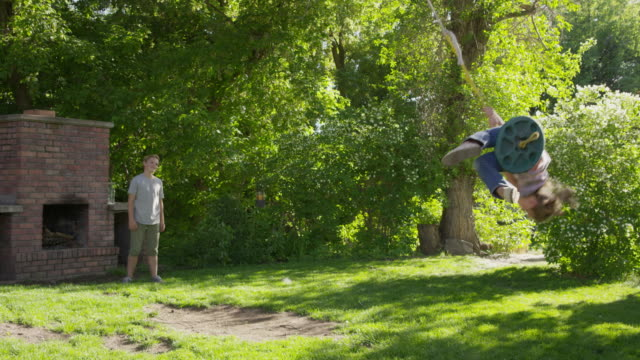 wide slow motion panning shot of boy pushing girl on rope swing / springville, utah, united states - springville utah stock-videos und b-roll-filmmaterial