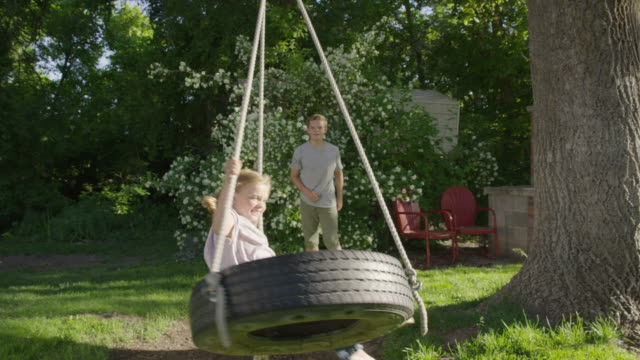 wide slow motion panning shot of boy pushing girl on tire swing / springville, utah, united states - springville utah stock videos & royalty-free footage