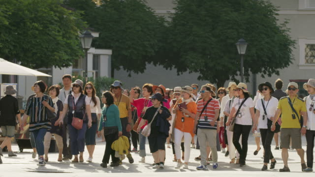 Wide slow motion panning shot of Chinese tourists walking in city / Salzburg, Austria