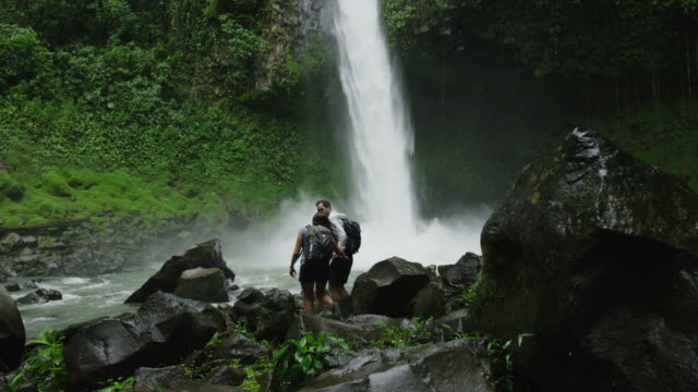 wide slow motion panning shot of couple admiring rain forest waterfall / arenal, la fortuna, costa rica - tourist video stock e b–roll