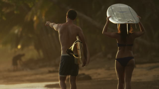 Wide slow motion panning shot of couple carrying surfboards on beach / Esterillos, Puntarenas, Costa Rica