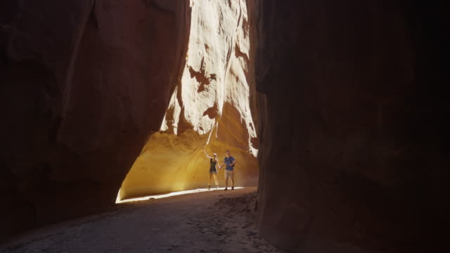wide slow motion panning shot of couple hiking in narrow canyon / escalante, utah, united states - escalante stock-videos und b-roll-filmmaterial