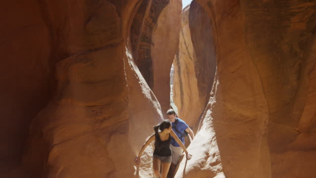 Wide slow motion panning shot of couple hiking in narrow slot canyon / Escalante, Utah, United States