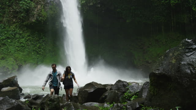 Wide slow motion panning shot of couple hiking near rain forest waterfall / Arenal, La Fortuna, Costa Rica
