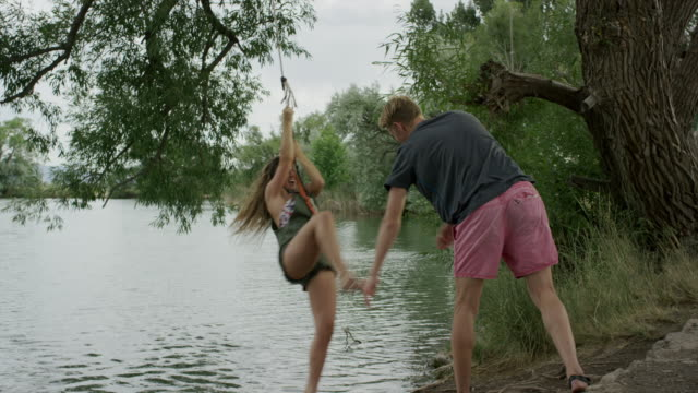 wide slow motion panning shot of couple playing at lake / mona, utah, united states - swinging stock videos & royalty-free footage