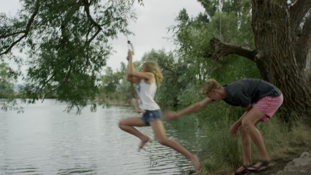wide slow motion panning shot of couple playing at lake / mona, utah, united states - rope swing stock videos & royalty-free footage