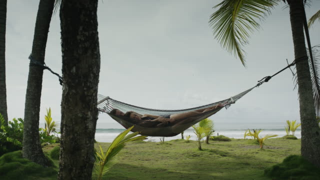 Wide slow motion panning shot of couple relaxing in hammock / Esterillos, Puntarenas, Costa Rica