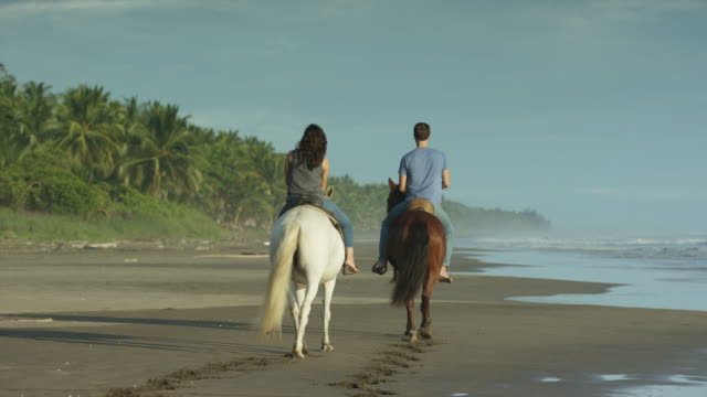 wide slow motion panning shot of couple riding horseback on beach / esterillos, puntarenas, costa rica - all horse riding stock videos & royalty-free footage