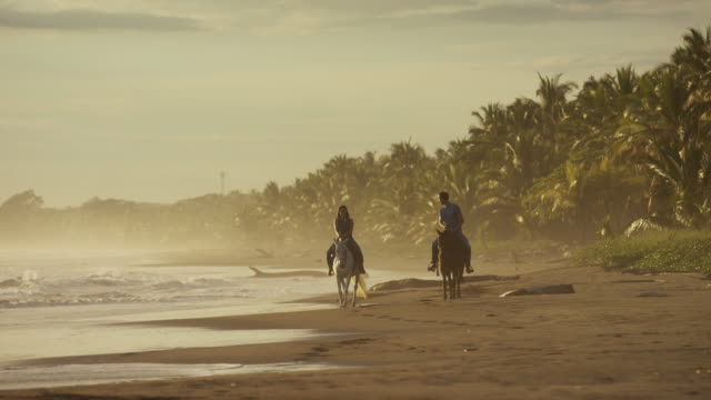 Wide slow motion panning shot of couple riding horseback on beach / Esterillos, Puntarenas, Costa Rica