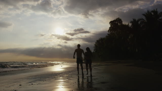 wide slow motion panning shot of couple running on beach at sunset / esterillos, puntarenas, costa rica - costa rica video stock e b–roll