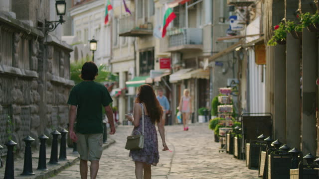 Wide slow motion panning shot of couple walking on cobblestone street / Veliko Tarnovo, Bulgaria
