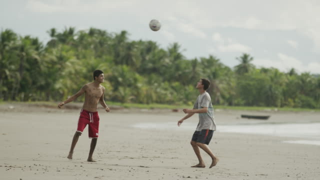 Wide slow motion panning shot of men playing with soccer ball on beach / Esterillos, Puntarenas, Costa Rica