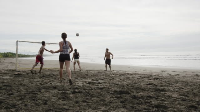 wide slow motion panning shot of people playing soccer on beach / esterillos, puntarenas, costa rica - puntarenas stock-videos und b-roll-filmmaterial