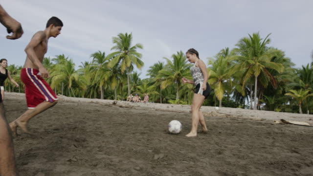 wide slow motion panning shot of people playing soccer on beach / esterillos, puntarenas, costa rica - 上半身裸点の映像素材/bロール