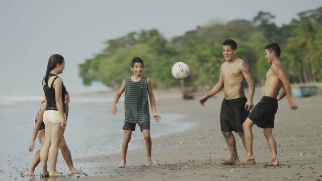 wide slow motion panning shot of people playing with soccer ball on beach / esterillos, puntarenas, costa rica - 上半身裸点の映像素材/bロール