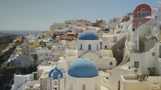wide slow motion panning shot of rooftops in hillside cityscape / oia, santorini, greece - oia santorini stock videos & royalty-free footage