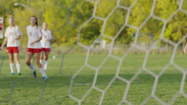 wide slow motion panning shot of soccer ball hitting net / springville, utah, united states - kicking stock videos & royalty-free footage