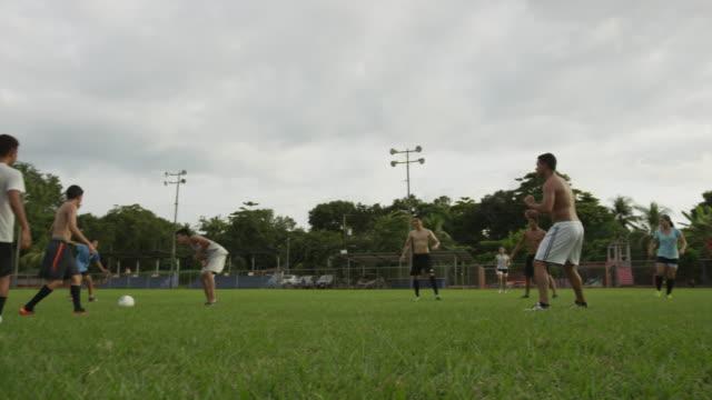 Wide slow motion panning shot of soccer player injured during game / Esterillos, Puntarenas, Costa Rica