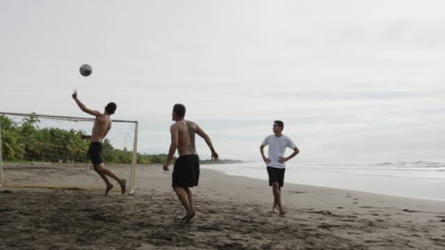 wide slow motion panning shot of soccer team playing on beach / esterillos, puntarenas, costa rica - geköpft stock-videos und b-roll-filmmaterial