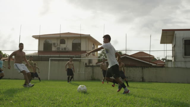 wide slow motion panning shot of soccer teams playing on field / esterillos, puntarenas, costa rica - puntarenas stock-videos und b-roll-filmmaterial