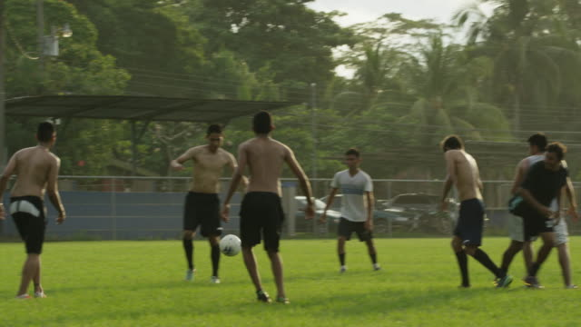 wide slow motion panning shot of soccer teams playing on field / esterillos, puntarenas, costa rica - 上半身裸点の映像素材/bロール