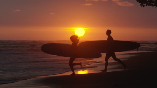 wide slow motion panning shot of surfers running to waves on beach at sunset / esterillos, puntarenas, costa rica - costa rica video stock e b–roll